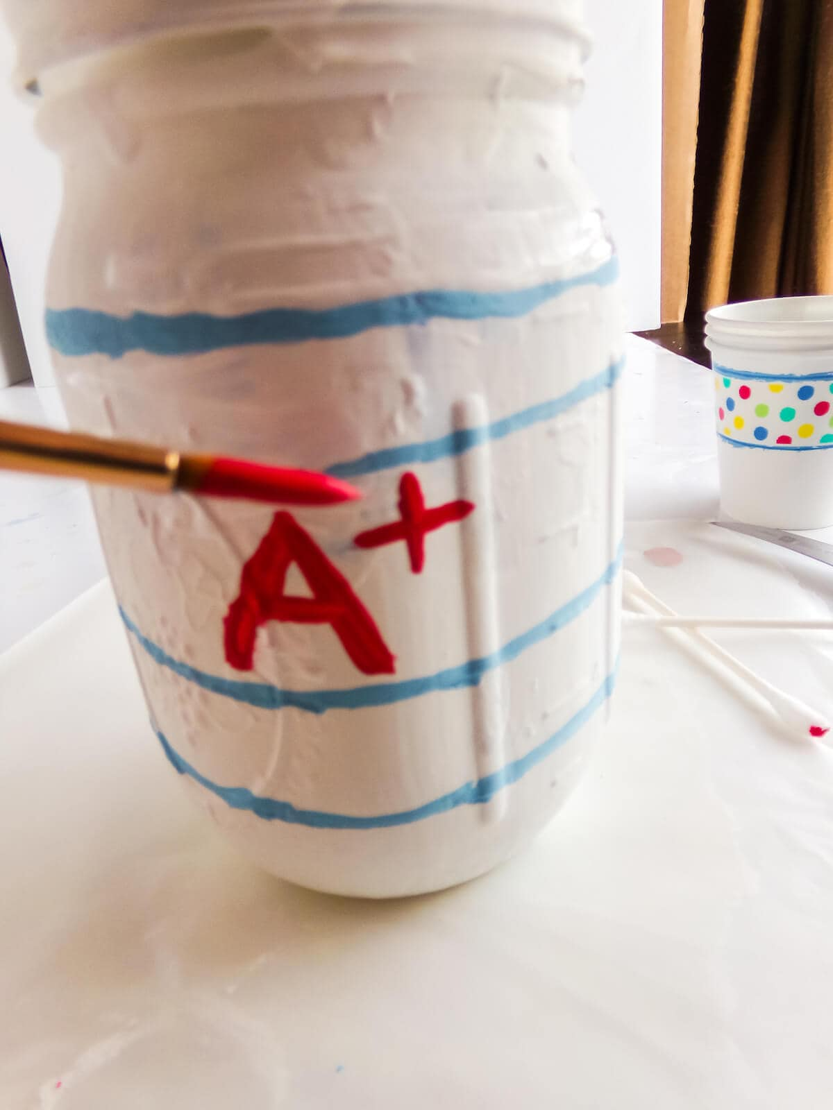 in-process step of painting a paper mason jar