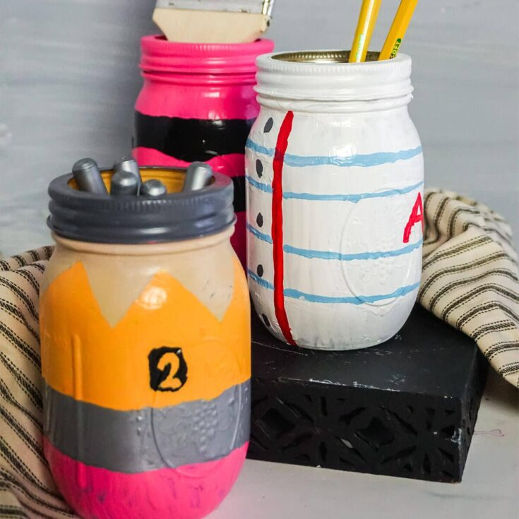 pencil paper and crayon painted jars on a table
